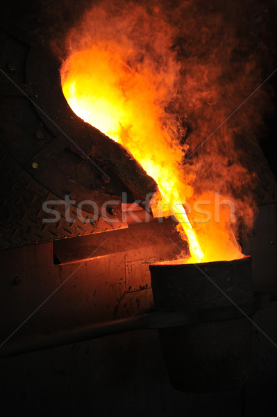 Foundry - molten metal poured from ladle for casting Stock photo © brozova