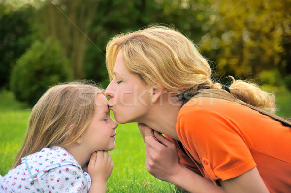Mother is kissing her daughter Stock photo © brozova