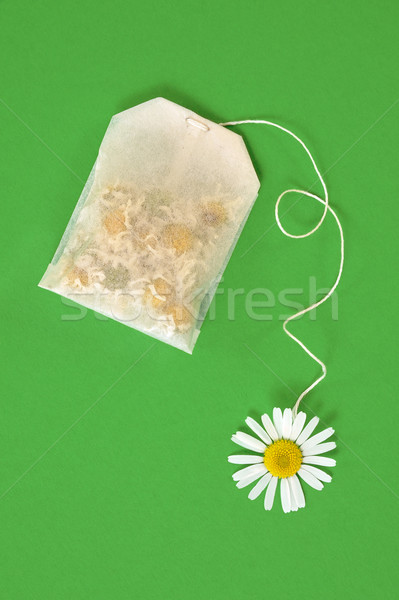 Bag of chamomile tea over green background - concept Stock photo © brozova