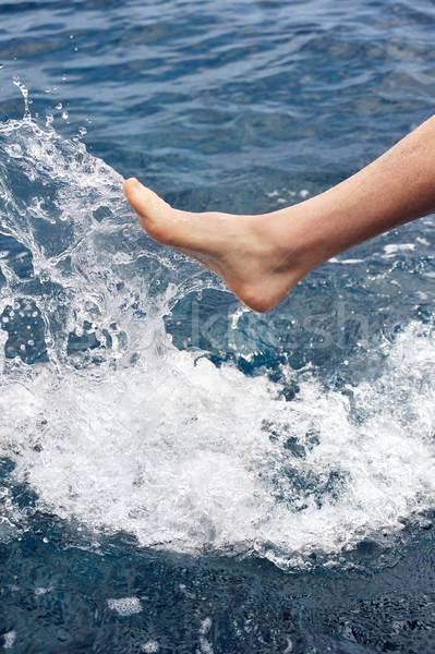 Foot of young man in water - splash Stock photo © brozova