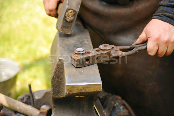 Blacksmith hammering hot steel on anvil Stock photo © brozova