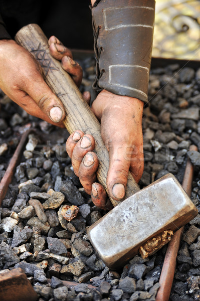 Detail of dirty hands holding hammer - blacksmith Stock photo © brozova