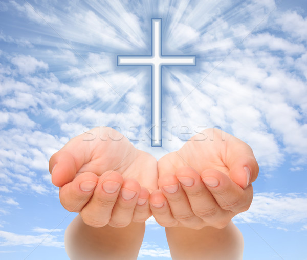 Hands holding Christian cross with light beams over sky Stock photo © brozova