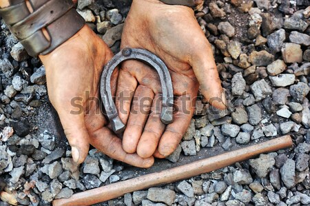 Detail of dirty hands holding horseshoe - blacksmith Stock photo © brozova