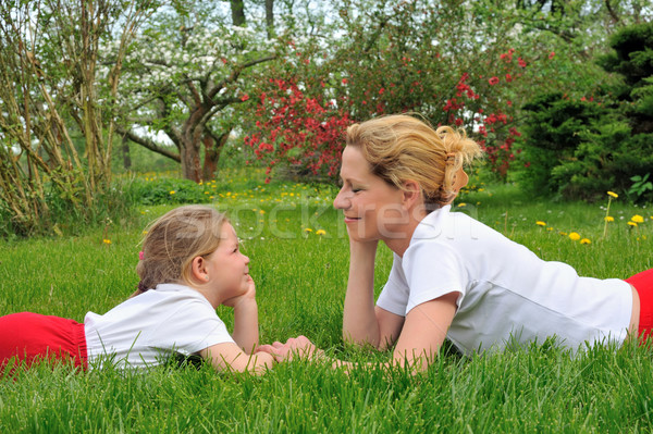 Young mother and daughter laying on the grass - practising Stock photo © brozova