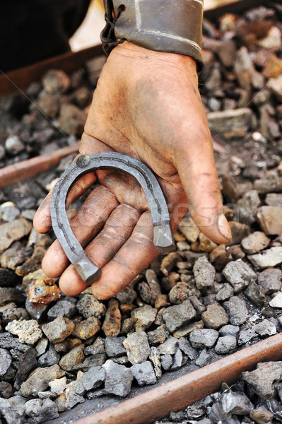 Stock photo: Detail of dirty hand holding horseshoe - blacksmith