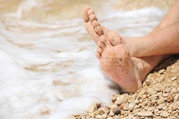 Relaxation on beach, detail of male feet Stock photo © brozova