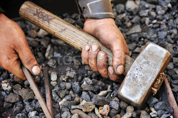 Stock photo: Detail of dirty hands holding hammer and rod - blacksmith