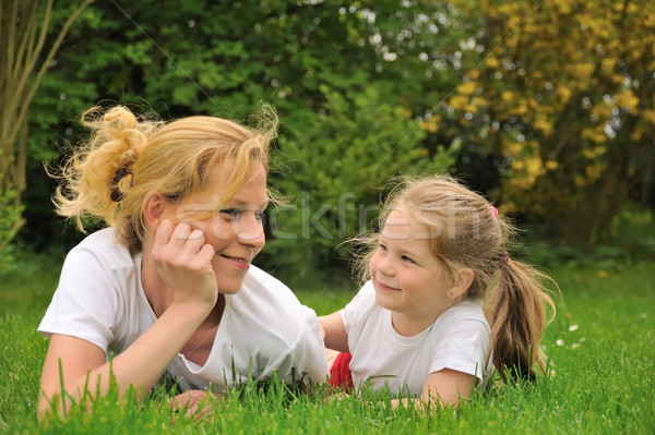 Young mother and daughter laying on the grass Stock photo © brozova