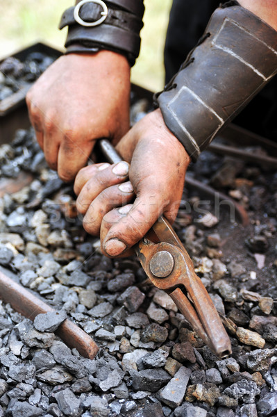 Detail of dirty hands holding pliers - blacksmith Stock photo © brozova