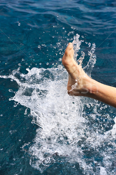Foot of young man in water - splash Stock photo © brozova