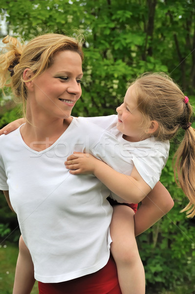 Young mother giving her child piggyback ride Stock photo © brozova