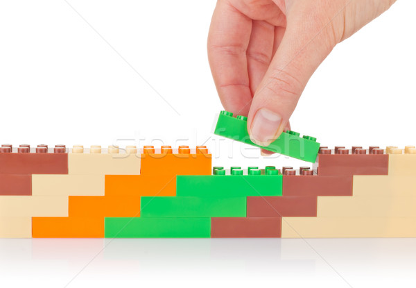 Hand build wall of colour toy block Stock photo © brulove