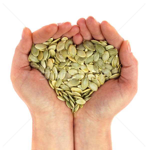 Seed of pumpkin in palm looks like heart. Stock photo © brulove