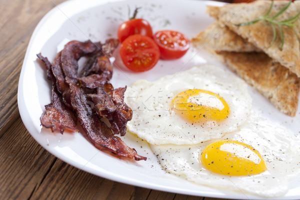 Delicious fried egg with spices, bacon, croutons and tomatoes on Stock photo © BrunoWeltmann