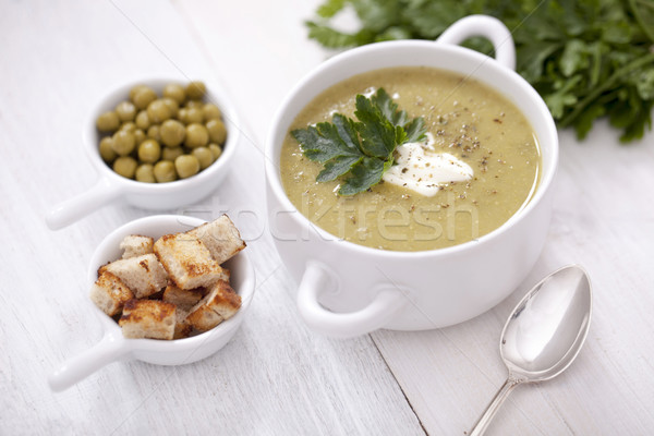 A delicious pea cream with aromatic spices on a wooden table. Stock photo © BrunoWeltmann