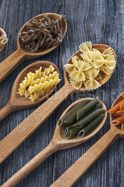 A set of raw pastas on spoons on a wooden table Stock photo © BrunoWeltmann