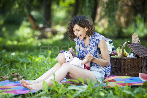Young beautiful mother sits with her daughter on blanket in park Stock photo © BrunoWeltmann