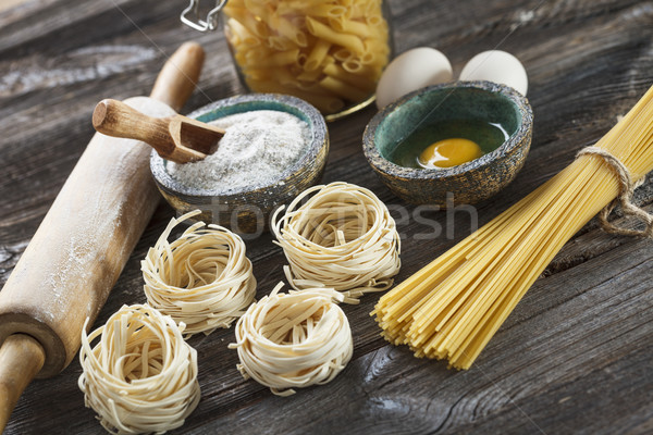 A set of raw pasta and addons on wooden table Stock photo © BrunoWeltmann