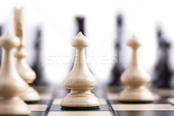 Stock photo: Chess pieces on a chessboard.