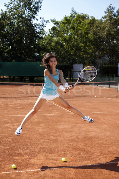 Young girl playing tennis on court.  Stock photo © BrunoWeltmann