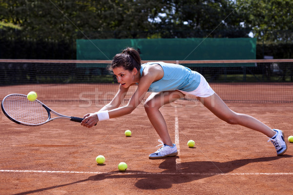 Young girl catching a ball in tennis court Stock photo © BrunoWeltmann