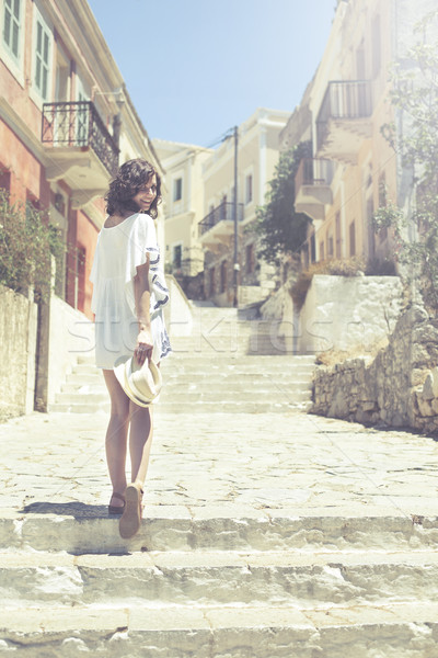 Beautiful girl bathed in sunshine walking in ancient city Symi Stock photo © BrunoWeltmann