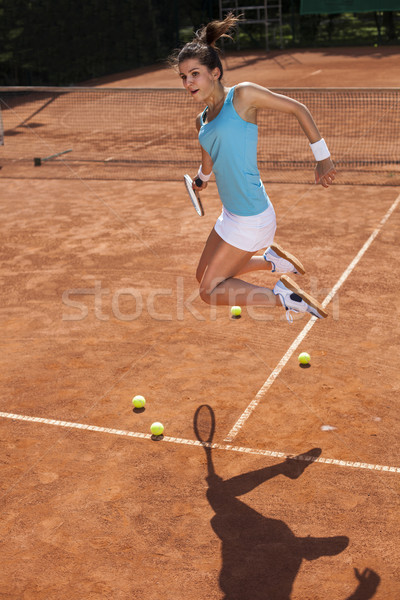 Young girl playing tennis at the beautiful weather Stock photo © BrunoWeltmann