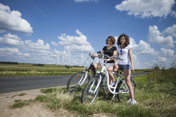 Twee mooie meisjes fiets tour rock Stockfoto © BrunoWeltmann