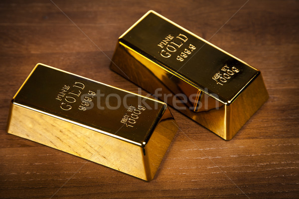 Two gold bars on wooden table Stock photo © BrunoWeltmann