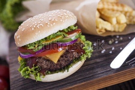 Beef burgers on a wooden board with chips and aromatic spices. Stock photo © BrunoWeltmann