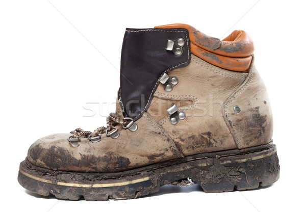 Old trekking boot in mud. Side view. Stock photo © BSANI