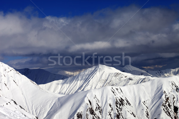 Snowy sunlit mountains and cloudy sky Stock photo © BSANI