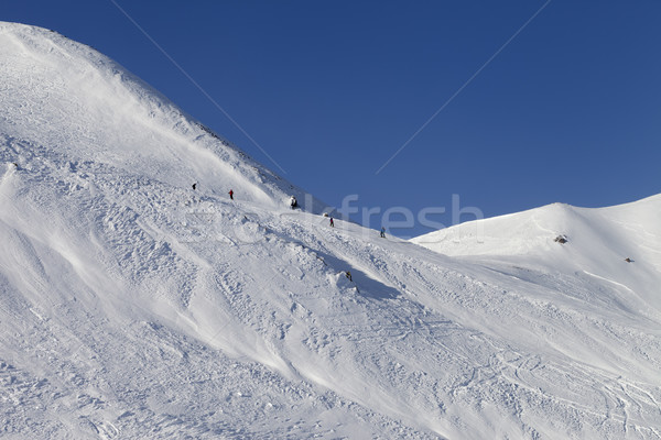 Stock photo: Skiers and snowboarders on ski piste