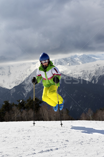Young skier jump with ski poles in sun winter mountains and clou Stock photo © BSANI