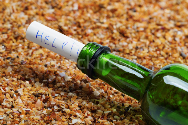 Bottle of wine with help message on sand in beach at sun summer  Stock photo © BSANI
