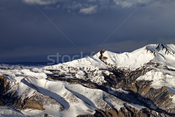 Winter mountains at sun evening and dark clouds Stock photo © BSANI