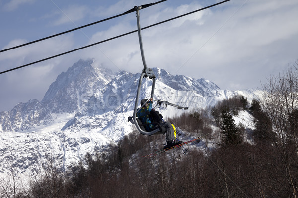 Skiers on ski-lift in snow mountains at winter sun day Stock photo © BSANI