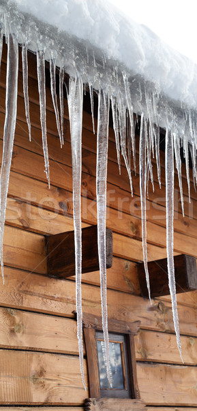 Wooden house with big icicles on snow-covered roof Stock photo © BSANI