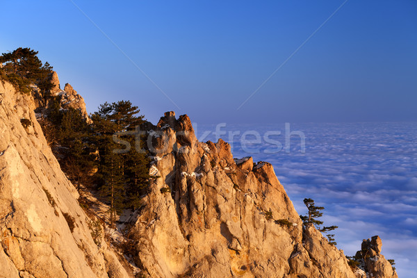 Sunlit rocks and sea in clouds at evening Stock photo © BSANI
