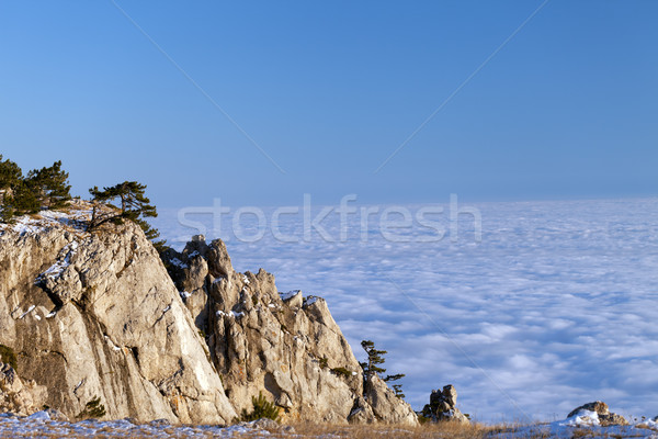 Sunlit cliffs and sea in clouds Stock photo © BSANI