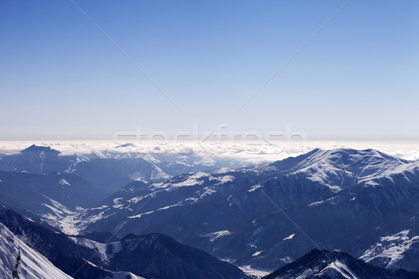 View from off-piste slope on snowy mountains in haze Stock photo © BSANI