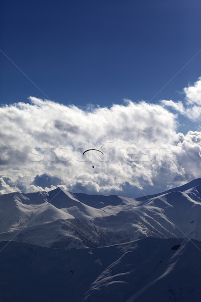 Winter mountain in evening and silhouette of parachutist Stock photo © BSANI
