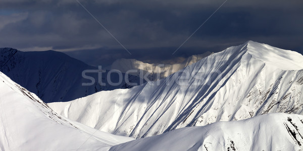 Panoramic view on snowy sunlit mountains and overcast sky Stock photo © BSANI