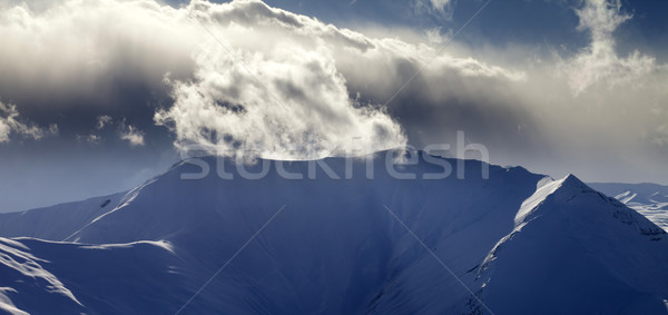 Panoramic view of mountains in sunset with sunlit clouds Stock photo © BSANI