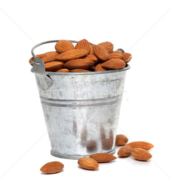 Tin bucket full of almonds on white background Stock photo © BSANI
