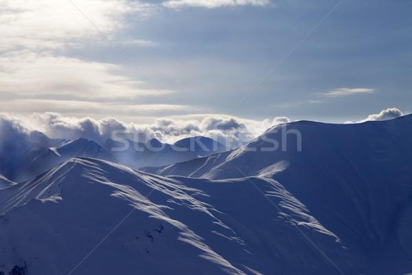 Snowy mountains in mist at sun evening Stock photo © BSANI