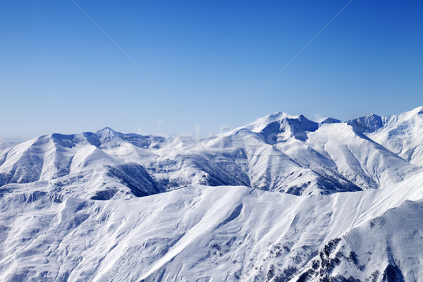 Snowy winter mountains and blue sky, view from ski slope Stock photo © BSANI