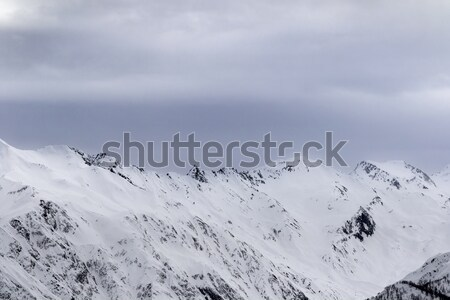 Snowy mountains in fog at gray morning Stock photo © BSANI