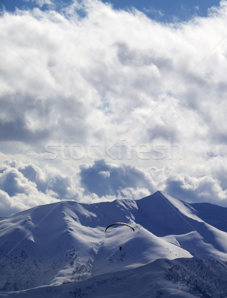 Evening sunlight mountain and silhouette of paraglider Stock photo © BSANI